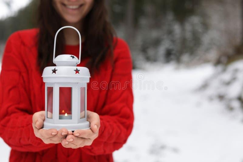 Фонарик удерживания женщины с горя свечой около снежного леса стоковые фотографии rf