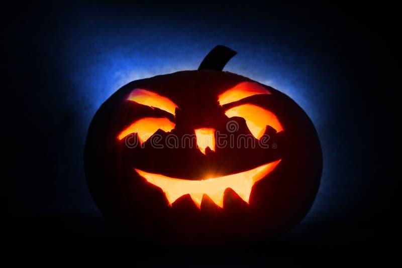 Фонарик jack головы тыквы хеллоуина с горящими свечами на голубой предпосылке стоковое фото