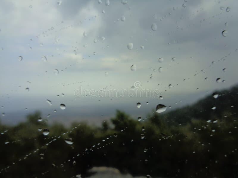 Фоновое изображение дождя падает на стеклянное окно стоковые изображения