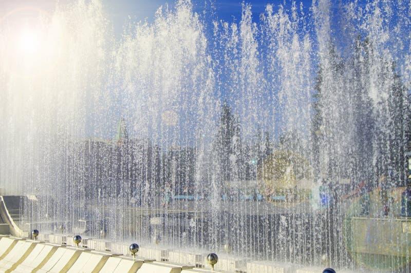 Фонтан города со струями воды и случайными людьми, взглядом до конца брызгает на солнечный летний день стоковые фото