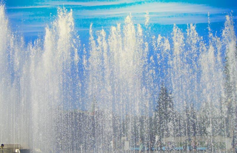 Фонтан города со струями воды и случайными людьми, взглядом до конца брызгает на солнечный летний день стоковые фотографии rf