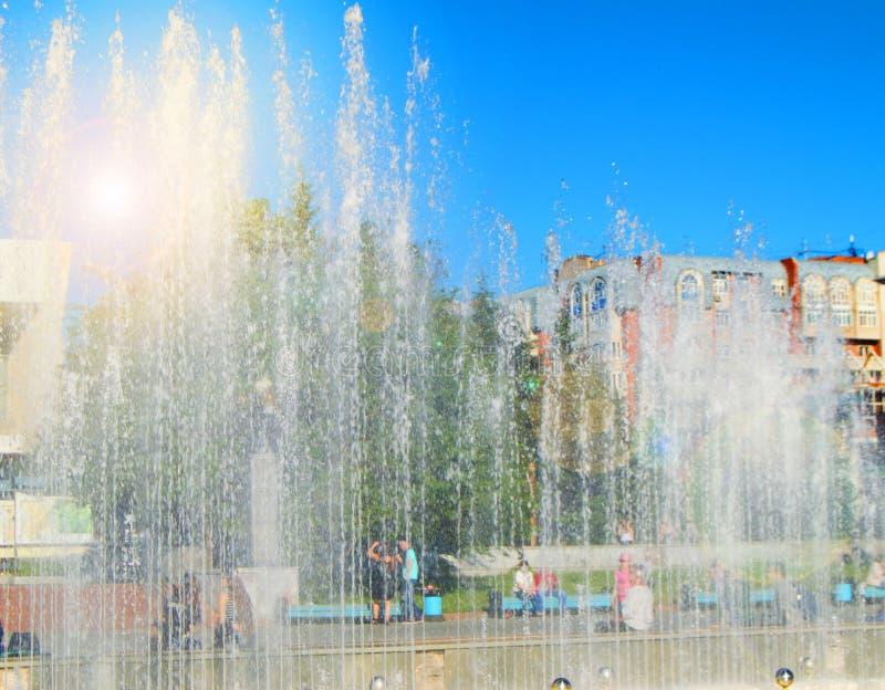 Фонтан города со струями воды и случайными людьми, взглядом до конца брызгает на солнечный летний день стоковое фото rf