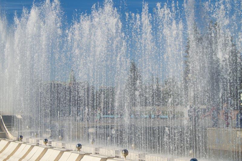Фонтан города с струями воды и случайными людьми, взглядом через брызг стоковая фотография rf