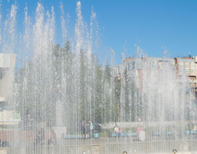 Фонтан города с струями воды и случайными людьми, взглядом через брызг стоковое изображение rf