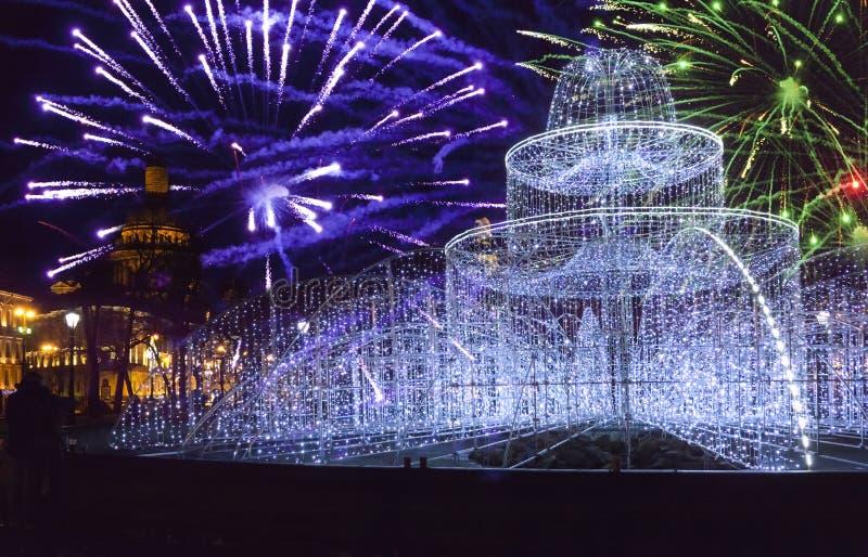 Фонтан от сияющих огней на квадрате перед собором St Исаак на фейерверках Новогодней ночи и рождества St Pete стоковое изображение rf
