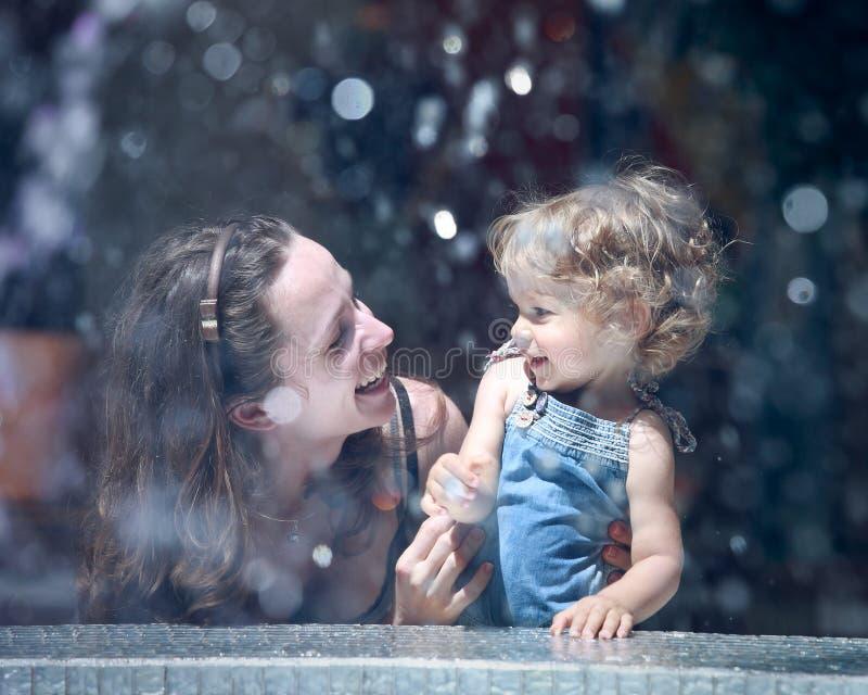 фонтан ребенка около женщины стоковые фото