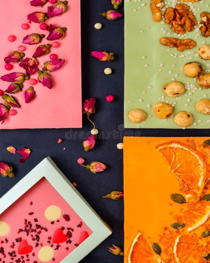 Фон шоколадной плитки с разнообразными сухофруктами и орехами на белом фоне дерева стоковые фото