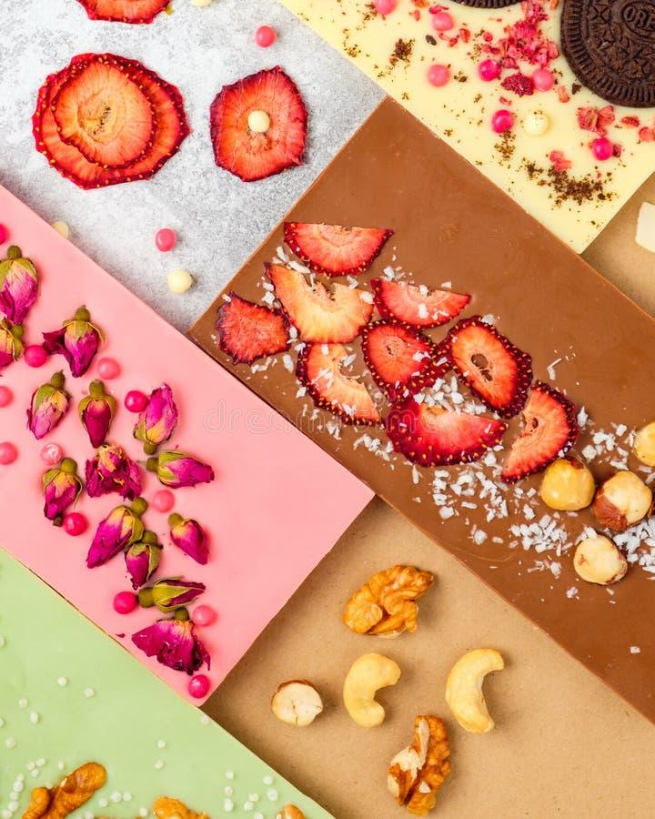 Фон шоколадной плитки с разнообразными сухофруктами и орехами на белом фоне дерева стоковые фотографии rf