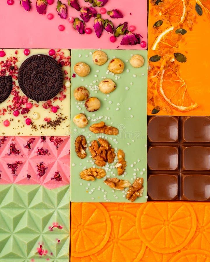 Фон шоколадной плитки с разнообразными сухофруктами и орехами на белом фоне дерева стоковая фотография rf