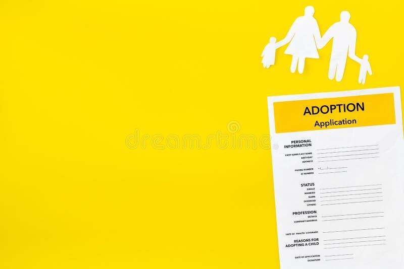 Форма для заявления для принимает ребенка на желтой насмешке взгляда сверху предпосылки вверх стоковая фотография rf