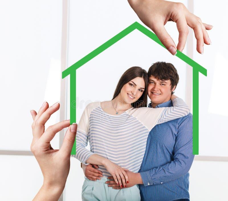 Форма зеленого дома с молодой семьей внутрь стоковая фотография rf