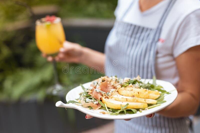 Форма официантки нося принося очень вкусному салату ее клиента стоковые фотографии rf
