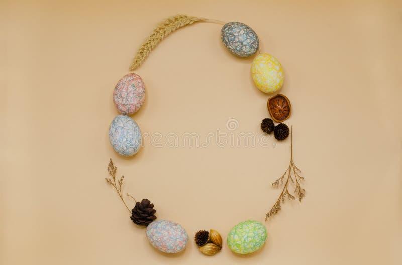 Форма пасхального яйца которые имеют красочные покрашенные яйца от crayon украшает с сухими листьями и цветками стоковое изображение rf