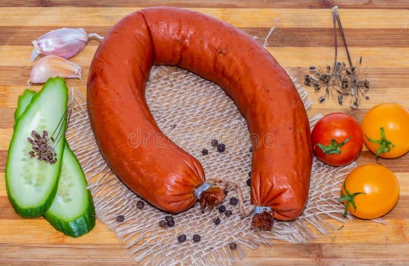 Форма свежей копченой сосиски horseshoe с беконом и отрезанным зеленым огурцом и 3 красные и желтая вишня томатов и стоковое фото rf