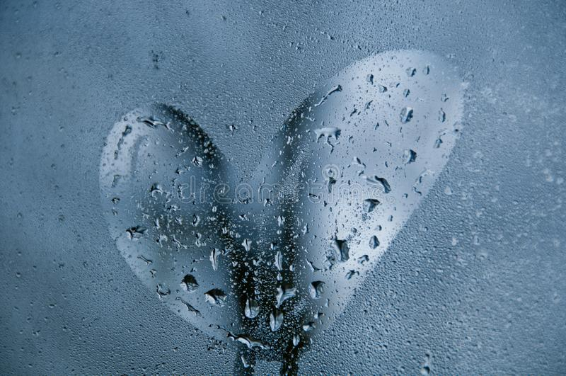 Форма сердца на окне капельки холодного туманного утра стоковые фото