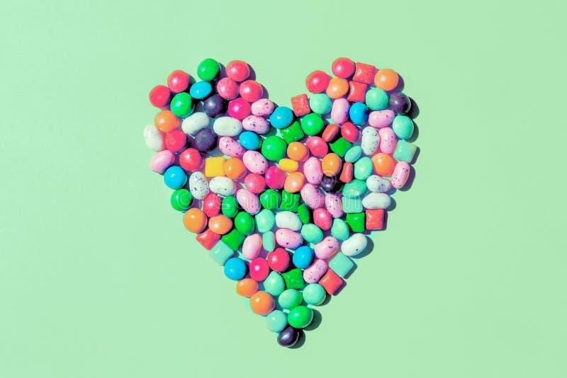 Форма сердца сделала небольших конфет colorfull на предпосылке мяты стоковая фотография rf