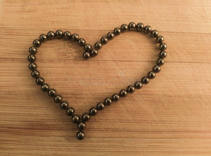 Форма сердца с подшипниками на деревянной предпосылке стоковое изображение