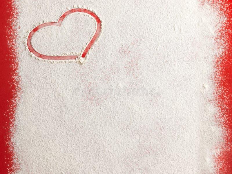 Форма сердца влюбленности валентинки красная в снеге на красной предпосылке стоковая фотография rf