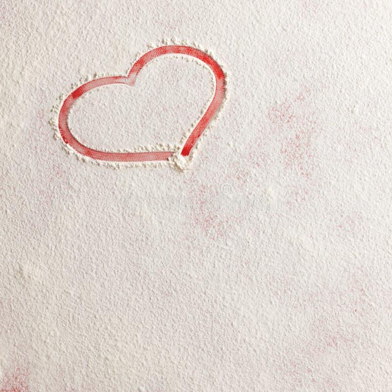 Форма сердца влюбленности валентинки красная в снеге на красной предпосылке стоковые фотографии rf