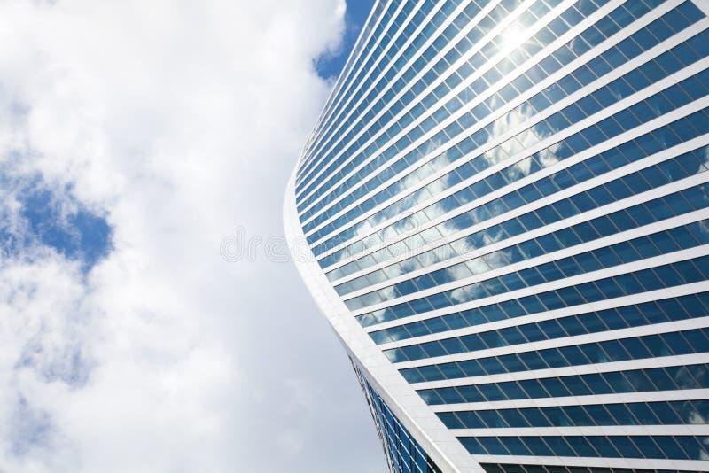Форма спирали стены небоскреба зеркала на голубом небе, белой предпосылке облаков, современном здании делового центра стоковое изображение