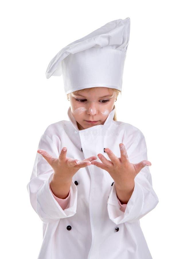 Форма шеф-повара девушки белая изолированная на белой предпосылке Смотреть раскрывать-наблюданный на floured ладонях Floured стор стоковые изображения
