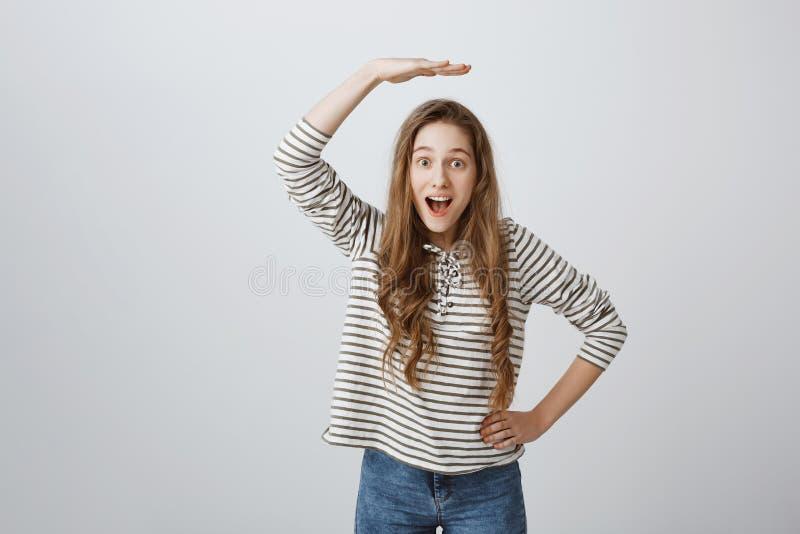 Формирующ масштаб как она надоедана в воздухе Крытая съемка excited симпатичного удерживания девушки подняла ладонь над головой стоковые фото