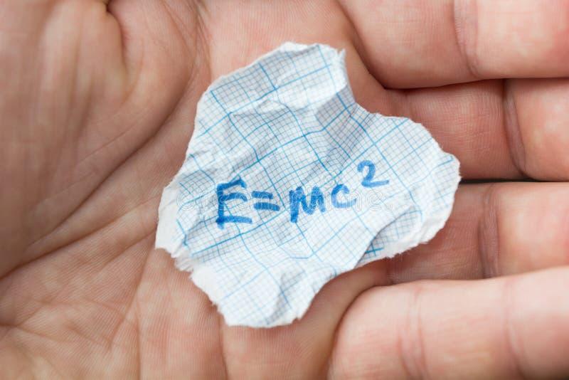 Формула e = mc2 в руке Шпаргалка стоковая фотография