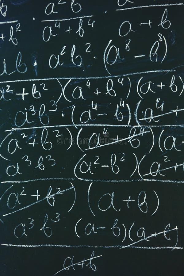 Формулы математик написанные белым мелом на предпосылке доски стоковая фотография