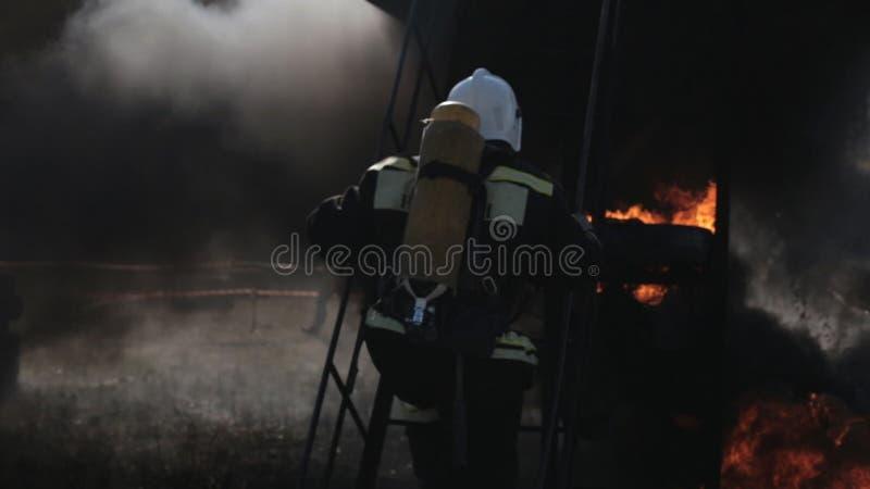 Формы носки пожарных около пожарной машины и бега акции видеоматериалы