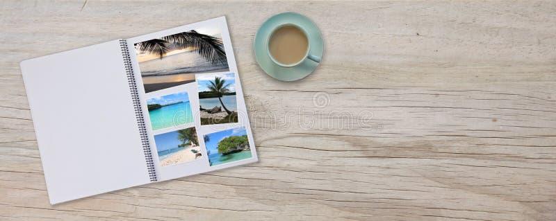 Фотоальбом с баннером на палубном столе с фотографиями путешествий и кофе или чаем в кубке стоковая фотография