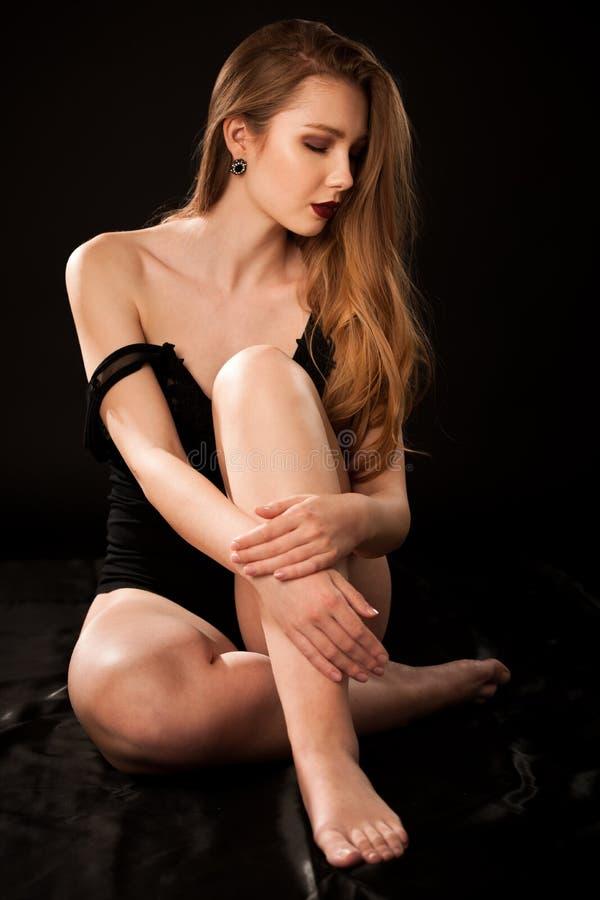 Фотография будуара красивой молодой дамы в черном теле над темной стильной предпосылкой стоковые изображения