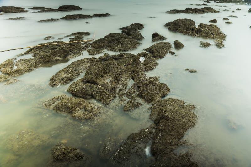 Фотография долгой выдержки волн на каменных водах пляжа окаймляет абстрактную предпосылку моря r стоковое изображение