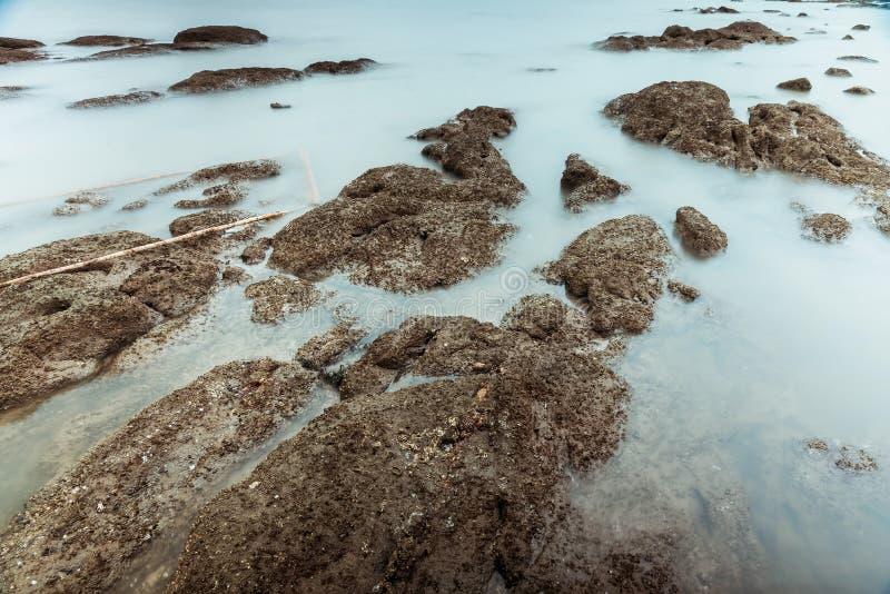 Фотография долгой выдержки волн на каменных водах пляжа окаймляет абстрактную предпосылку моря r стоковое фото