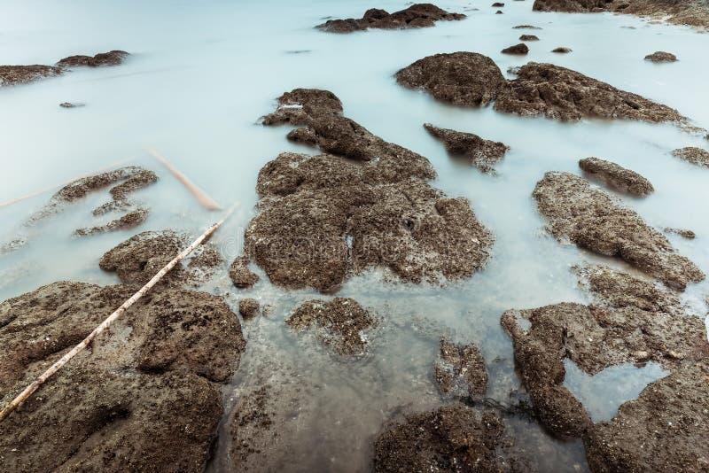 Фотография долгой выдержки волн на каменных водах пляжа окаймляет абстрактную предпосылку моря r стоковая фотография rf
