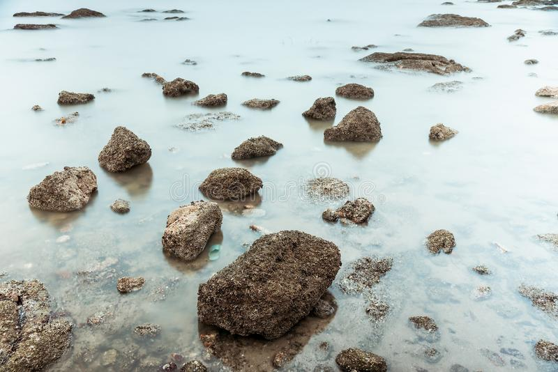 Фотография долгой выдержки волн на каменных водах пляжа окаймляет абстрактную предпосылку моря r стоковые фотографии rf