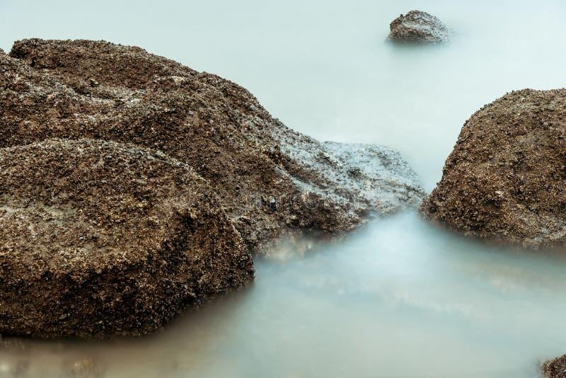 Фотография долгой выдержки волн на каменных водах пляжа окаймляет абстрактную предпосылку моря r стоковые изображения rf