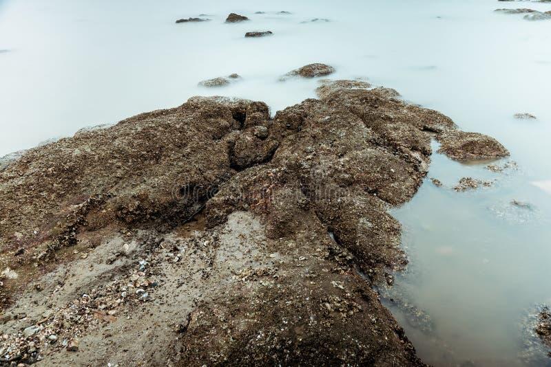Фотография долгой выдержки волн на каменных водах пляжа окаймляет абстрактную предпосылку моря r стоковые изображения