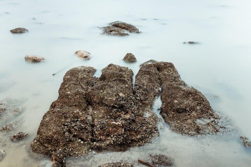 Фотография долгой выдержки волн на каменных водах пляжа окаймляет абстрактную предпосылку моря r стоковое фото rf