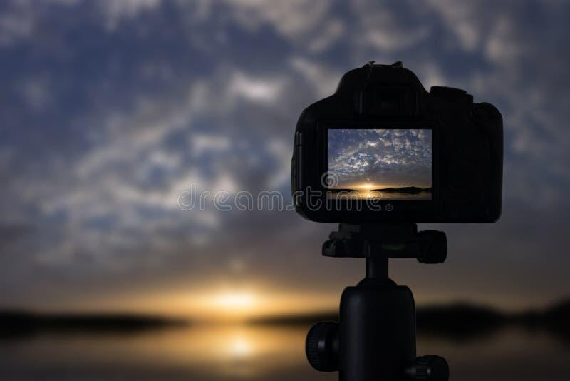 Фотография захода солнца Камера с заходом солнца треноги Заход солнца стоковые фотографии rf