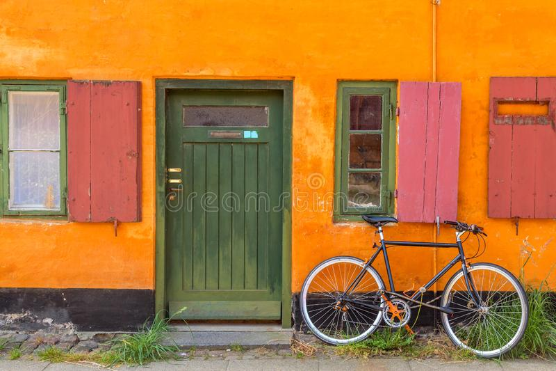 Фотография Копенгагена. Старый желтый дом района Нюбодер с велосипедоРстоковое изображение rf