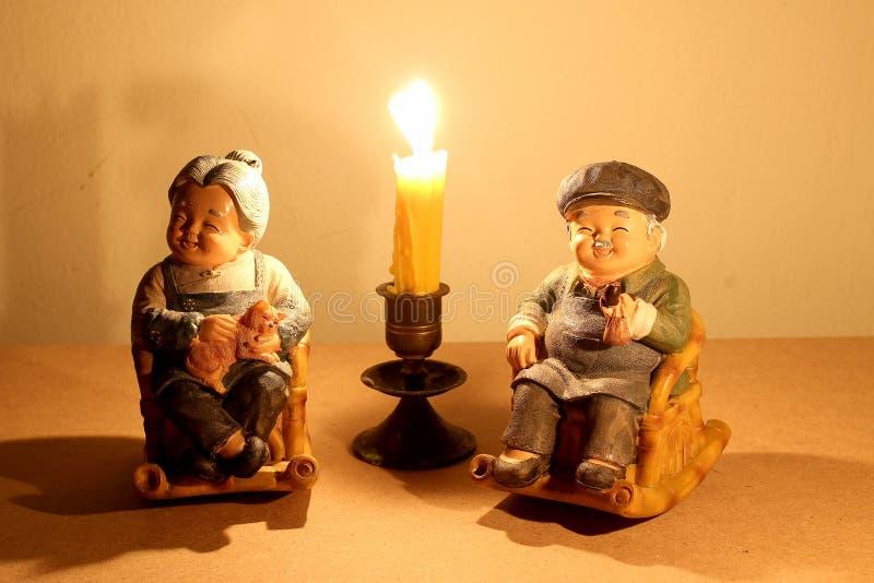 Фотография натюрморта при симпатичная старшая кукла пар распологая тряся бамбуковый стул с светом свечи в темноте на bac древесин стоковая фотография rf