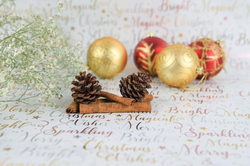 Фотография рождества цветков с конусами сосны яркого блеска и безделушек на предпосылке упаковочной бумаги xmas стоковые изображения