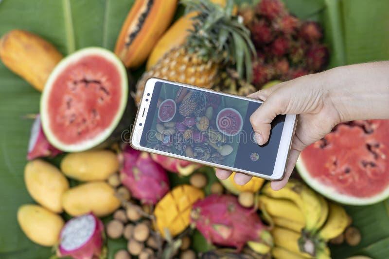 Фотография телефона взятия руки женщины тропических плодов Сладкое манго, папапайя, pitahaya, банан, арбуз, ананас Сырцовый vegan стоковое фото rf