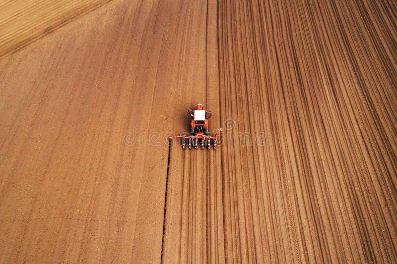 Фотография трутня трактора с сеялкой работая в поле стоковое изображение rf