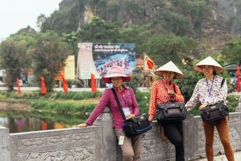 Фотографы женщин нося туристов конической шляпы ждать для того чтобы принять фото около Trang с горой на заднем плане стоковые фото