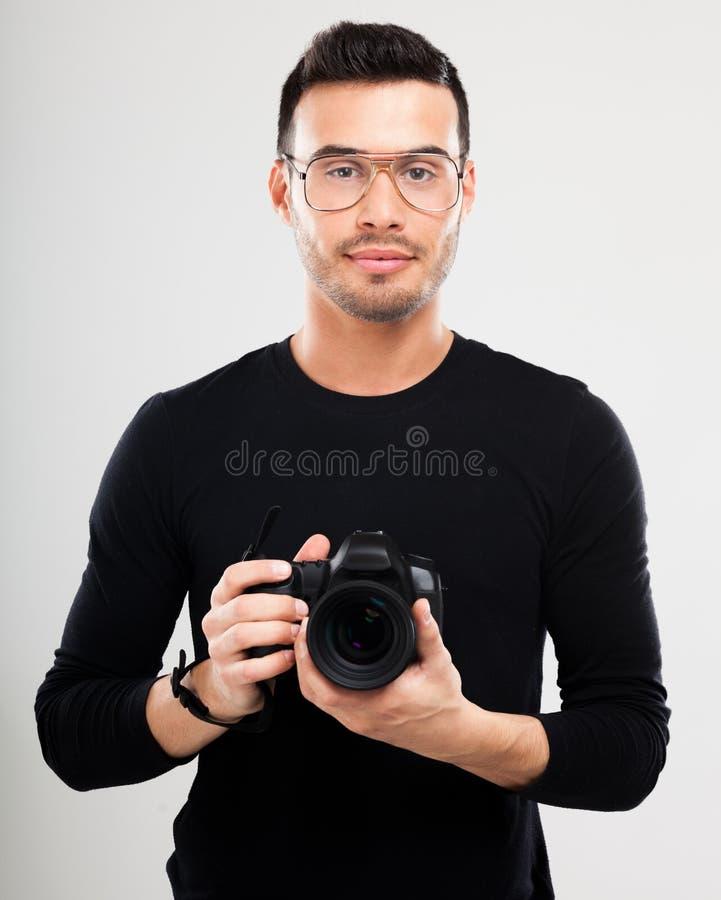 Фотограф держа зеркальную камеру стоковое фото