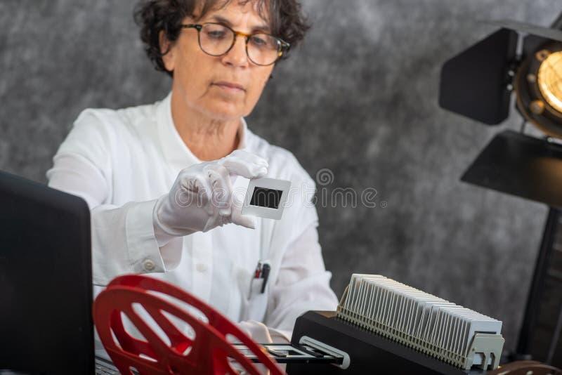 Фотограф женщины переводит скольжение в цифровую форму фильма для сохранения стоковые изображения rf