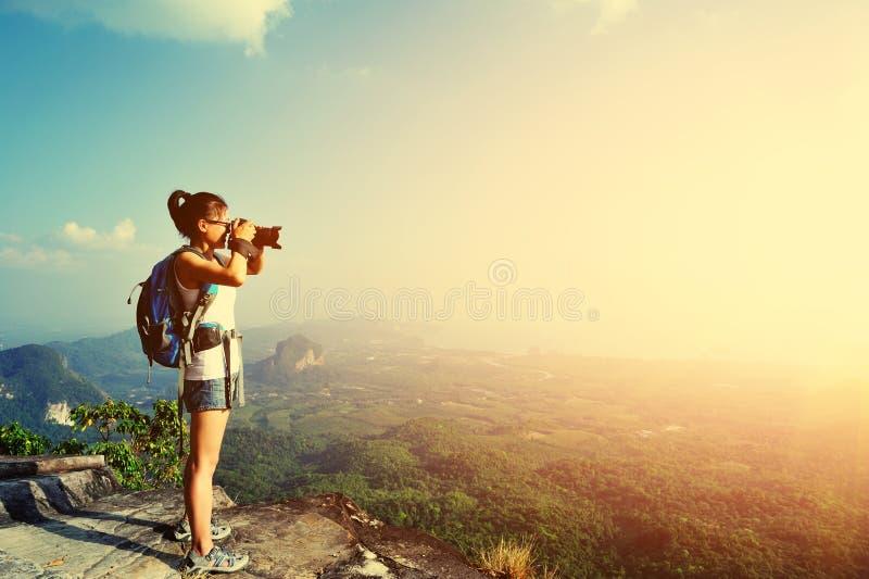 Фотограф женщины принимая фото на горный пик стоковое изображение rf