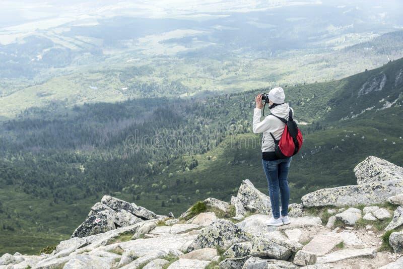Фотограф женщины принимая фото на горный пик стоковое изображение