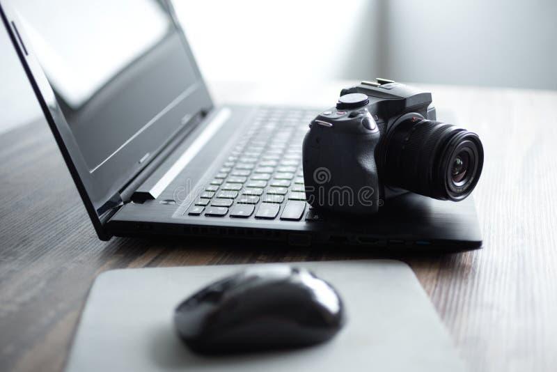 Фотограф или концепция фотографии запаса, цифровая черная камера около ноутбука на рабочем месте стола стоковое фото